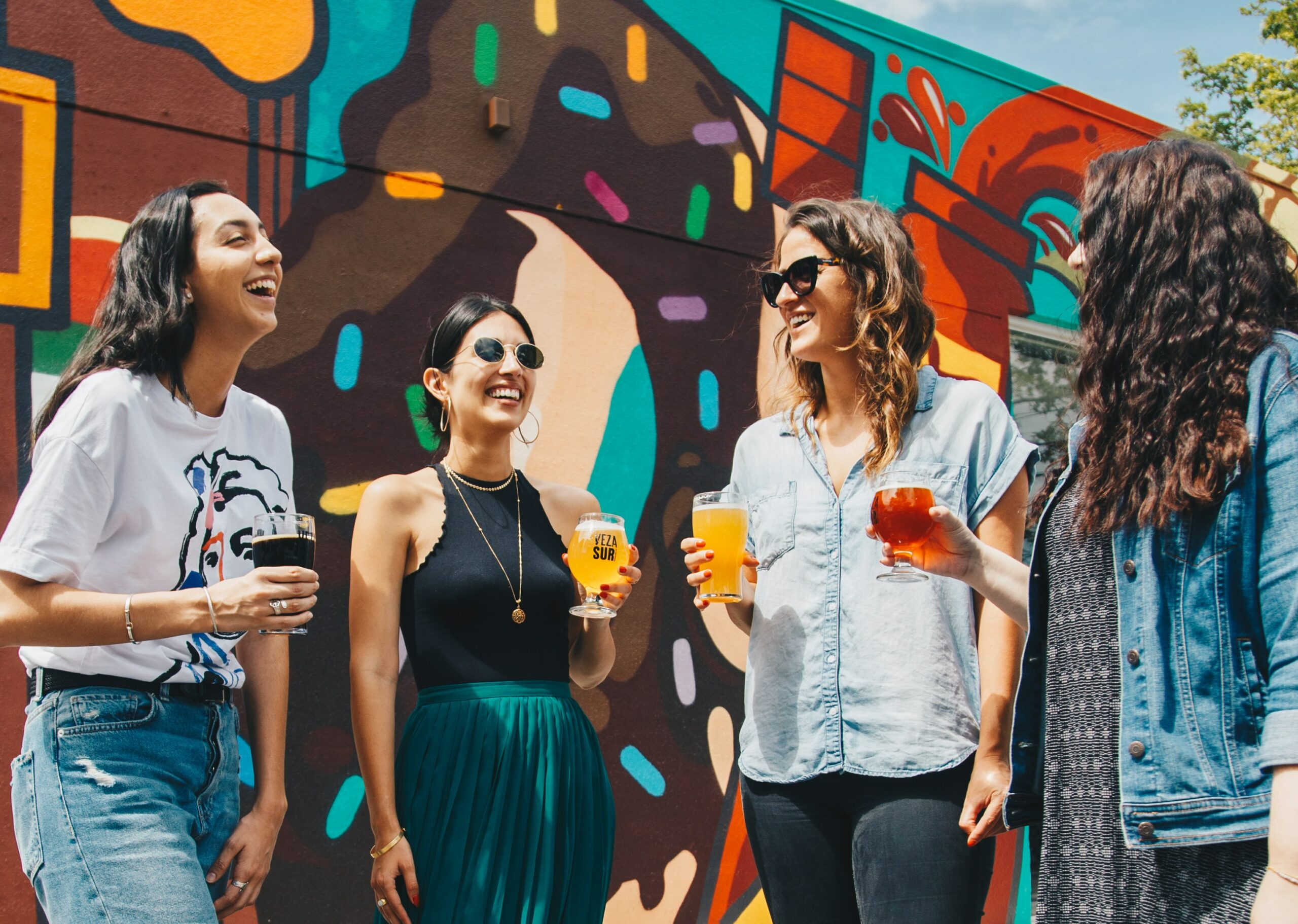 four women holding drinks against a graffiti painted wall
