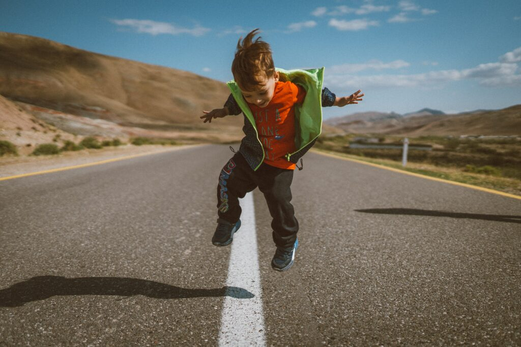 young kid jumping mid air in the middle of a country highway