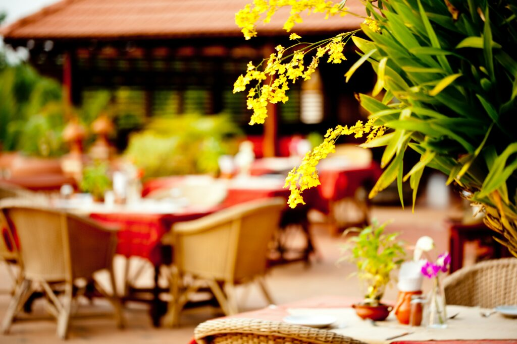 outdoor restaurant in asia with yellow orchid in foreground