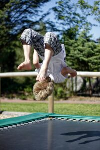 boy doing back-flip on outdoor trampolline