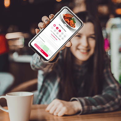 young girl in coffee shop wearing flannel shirt holding a mobile phone displaying the flex rewards digital punch card app