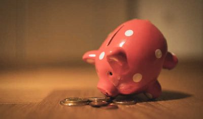 pink porcelain piggy bank with snout pointing at gold coins on a wooden table